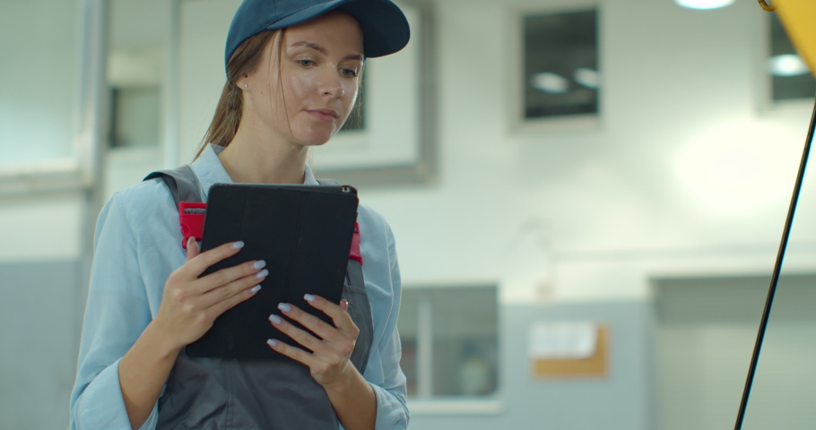 Female car mechanic using a digital tablet while doing routine maintenance check-up on a car in a garage.