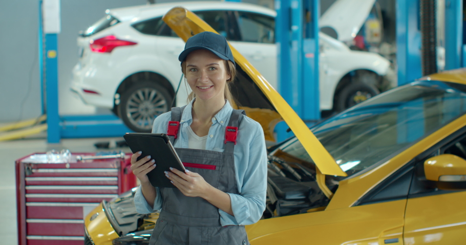 Female car mechanic using tablet device in big garage with cars. Beautiful woman using tablet, then smiling to camera in car workshop.