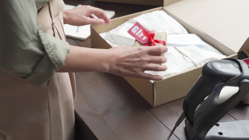 Female online store small business owner worker packing package post shipping ecommerce retail order gift in box preparing forwarding delivery parcel on table. Drop ship service concept, close up view Royalty-Free Stock Footage #1060888639