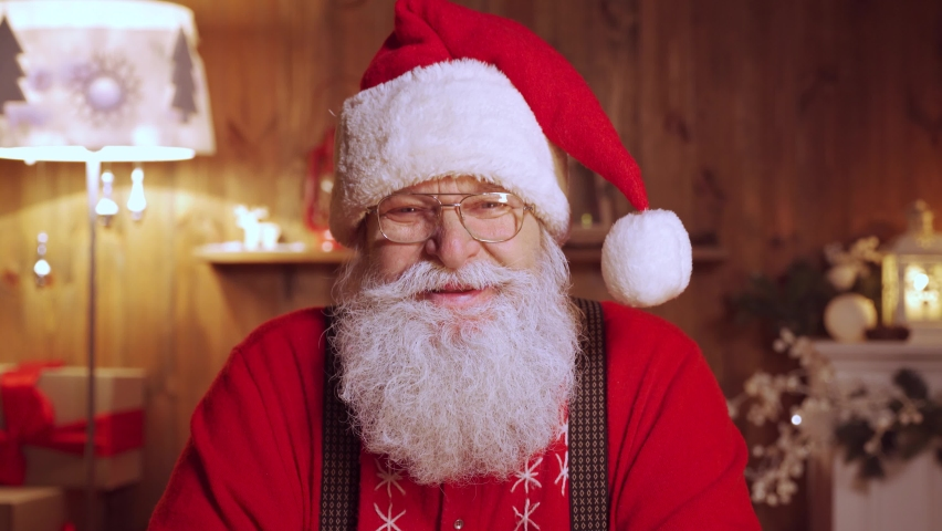Headshot close up portrait of funny old kind bearded Santa Claus face wearing hat, glasses, looking at camera, laughing. Saint Nicholas greeting on Merry Christmas, Happy New Year at home on xmas eve.