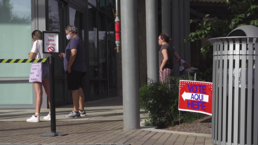 Austin, Texas October 16 2020: Voters stand in line outside polling or voting place in downtown during early voting in Austin Texas, bilingual sign is visible, election scrutinized for voter fraud