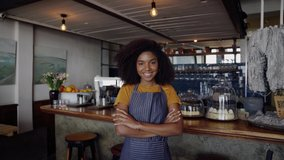 Clip of exquisite mixed raced cafe owner smiling crossed armed standing in trendy coffee shop.