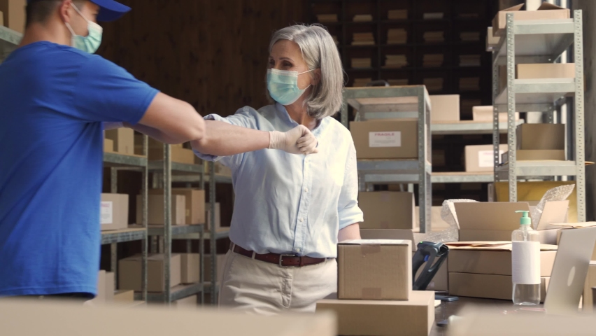 Warehouse workers wears masks gives elbow bump at meeting. Female supervisor greets male courier deliverer takes shipping parcels delivery boxes. Covid 19 healthcare protection social distance at work Royalty-Free Stock Footage #1060892449
