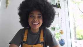 Young happy African American mixed race hipster vlogger woman waving hand looking at webcam talking to camera sit at table video conference calling in virtual chat meeting with social distance friend.