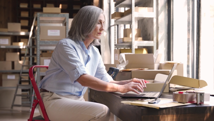 Older female dropshipping business owner using laptop talking on phone in warehouse. Mature woman seller entrepreneur checking online order selling on website confirming ecommerce shipping delivery.