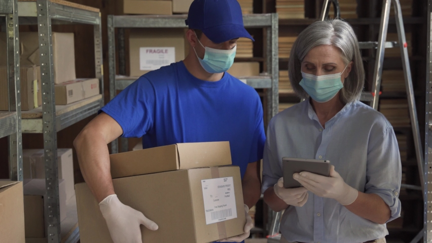 Female manager supervisor wearing face mask using digital tablet talking to male courier holding shipping parcels boxes discuss delivery walking in warehouse. Covid 19 safety social distance at work. Royalty-Free Stock Footage #1060892494