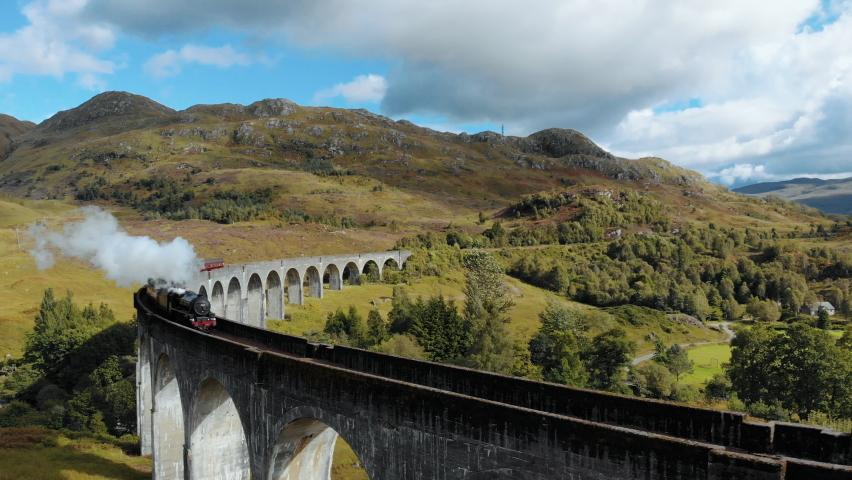 Aerial shot of a train crossing a beautiful bridge in a Scottish hill through a sunny landscape.   Shutterstock HD Video #1060894282