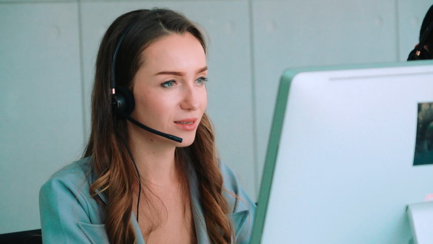 Business people wearing headset working in office to support remote customer or colleague. Call center, telemarketing, customer support agent provide service on telephone video conference call. Royalty-Free Stock Footage #1060898623