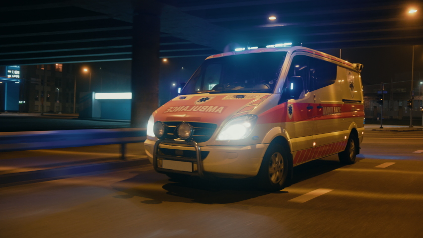 Parallel Moving Footage of an Ambulance Vehicle with Working Strobe Light and Signal Driving to Emergency Call on a City Urban Street at Night. Emergency Paramedics Rescue Van with Medical Cross Logo. Royalty-Free Stock Footage #1060901068