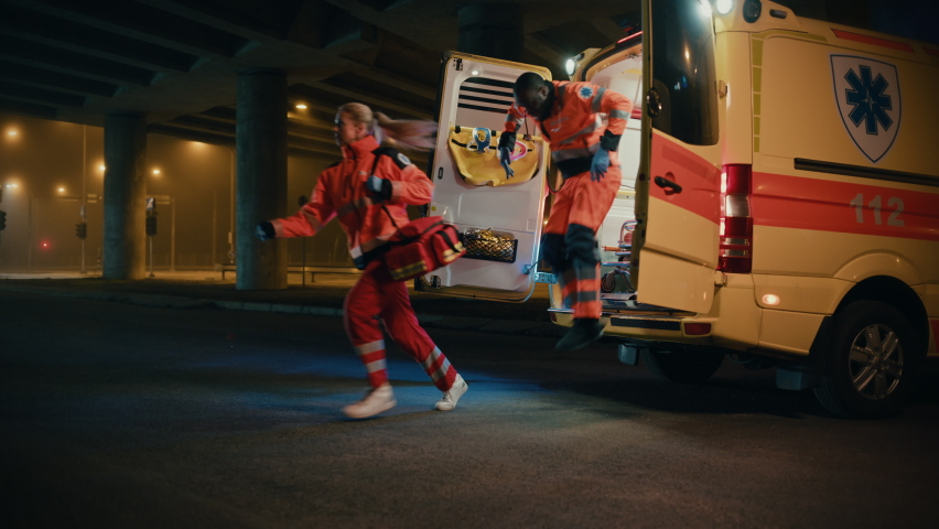Team of EMS Paramedics Quickly Jump Out from Ambulance Vehicle. Female Doctor Brings First Aid Kit. Emergency Care Assistants Arrived on the Scene of a Traffic Accident on a Street at Night. Royalty-Free Stock Footage #1060901089