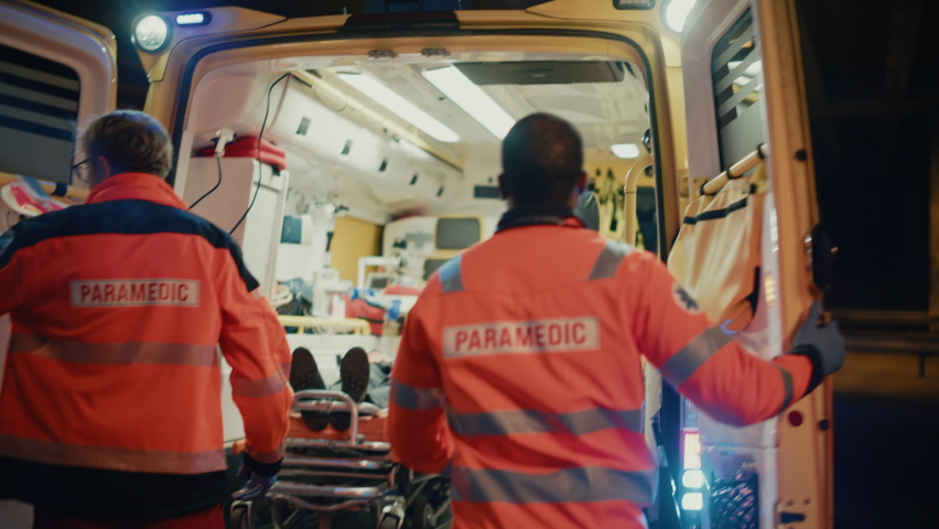 Team of EMS Paramedics React Quick to Provide Medical Help to Injured Patient and Get Him in Ambulance on a Stretcher. Emergency Care Assistants Arrived on the Scene of a Traffic Accident on a Street. Royalty-Free Stock Footage #1060901110