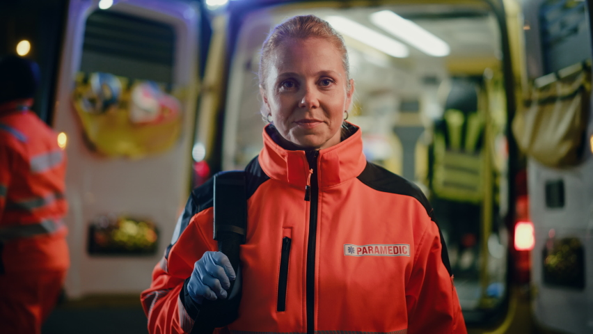 """Portrait of a Female EMS Paramedic Proudly Standing in Front of Camera in High Visibility Medical Orange Uniform with """"Paramedic"""" Text Logo. Successful Emergency Medical Technician or Doctor at Work. Royalty-Free Stock Footage #1060901125"""
