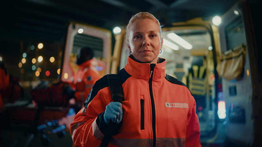 """Portrait of a Female EMS Paramedic Proudly Standing in Front of Camera in High Visibility Medical Orange Uniform with """"Paramedic"""" Text Logo. Successful Emergency Medical Technician or Doctor at Work. Royalty-Free Stock Footage #1060901128"""