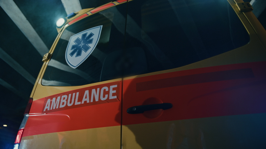 Team of EMS Paramedics Quickly Jump Out from Ambulance Vehicle. Female Doctor Takes First Aid Kit. Emergency Care Assistants Arrived on the Scene of a Traffic Accident on a Street at Night. Royalty-Free Stock Footage #1060901170