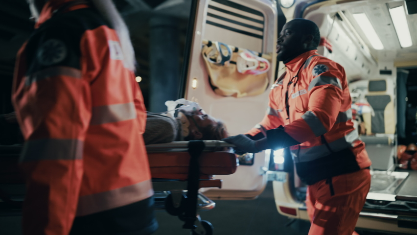 Team of EMS Paramedics React Quick to Bring Injured Patient to Healthcare Hospital and Get Him Out of Ambulance on a Stretcher. Emergency Care Assistants Help Young Man to Stay Alive After Accident. Royalty-Free Stock Footage #1060901173