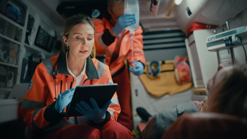 Female EMS Professional Paramedic Using Tablet Computer to Fill a Questionnaire for the Injured Patient on the Way to Hospital. Emergency Care Assistant Comforting the Patient in an Ambulance. Royalty-Free Stock Footage #1060901200