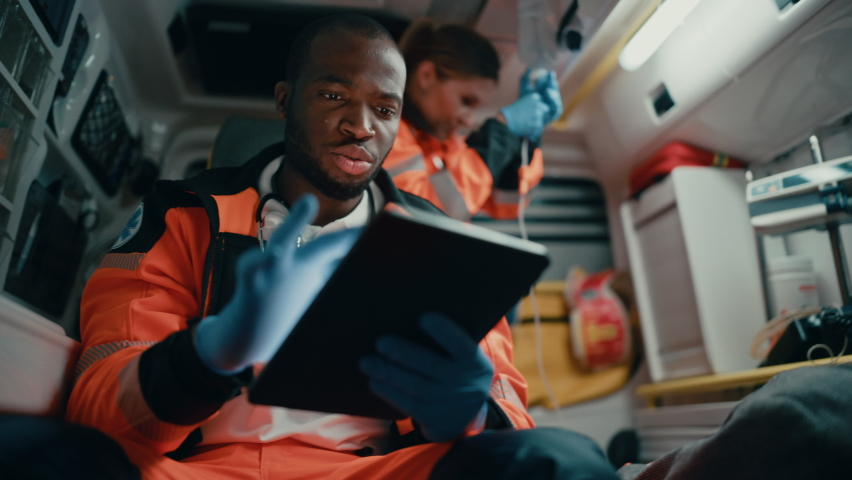 Black African American EMS Professional Paramedic Using Tablet Computer to Fill a Questionnaire for the Injured Patient on the Way to Hospital. Emergency Medical Care Assistant Works in an Ambulance. Royalty-Free Stock Footage #1060901215