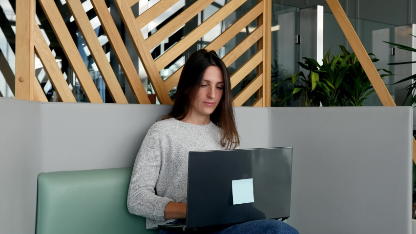 Smiling young business woman, using laptop, sitting at home office table, rejoicing at the result. The woman dances near the laptop and rejoices. Confirming online website shopping order delivery