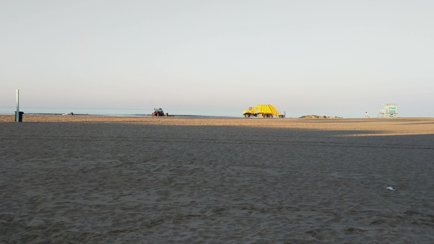 Morning beach cleaning tractor and garbage collection at Santa Monica pier handheld static shot | Shutterstock HD Video #1060916134