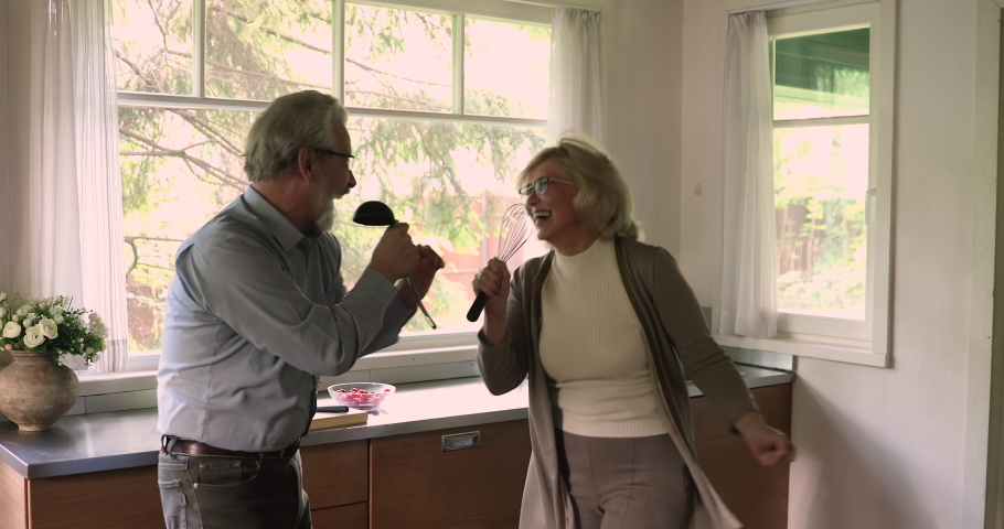 50s grey haired wife and husband hold hands while listen music sing song using kitchenware like microphones enjoy karaoke together standing in kitchen feels happy. Hobby, untroubled retirees concept