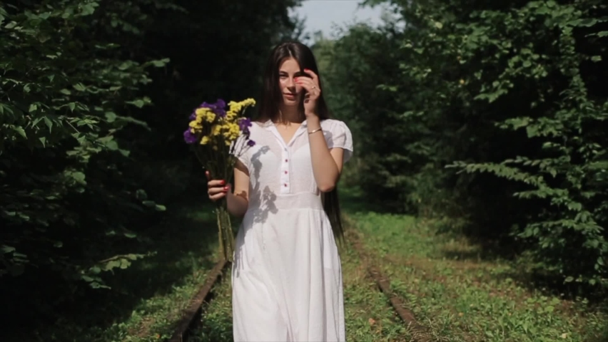 A beautiful young woman in a white dress and flowers in her hands against violence and cruelty at peaceful protests in Belarus walks against the backdrop of green trees. Slow motion