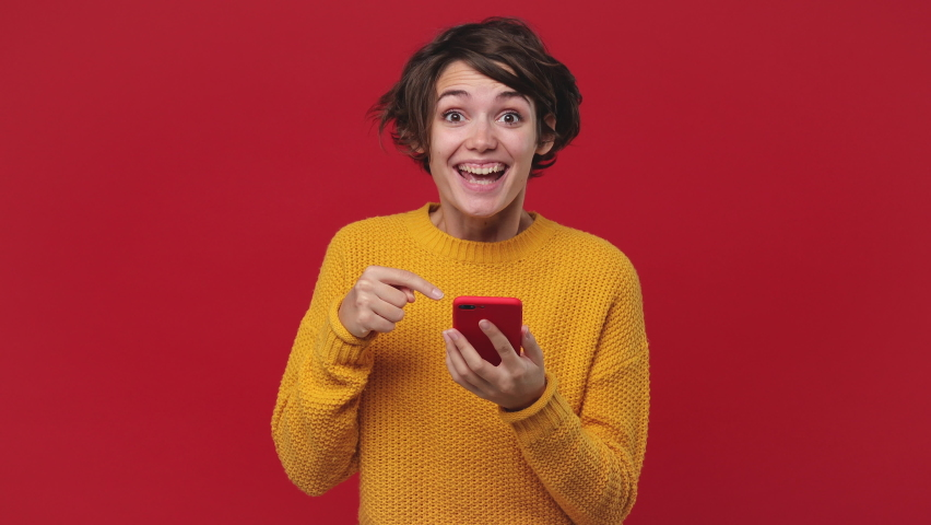 Smiling shocked happy win beautiful young woman 20s years old in yellow sweater posing isolated on red background in studio. People lifestyle concept. Look surprised wow hold using mobile cell phone Royalty-Free Stock Footage #1060922143