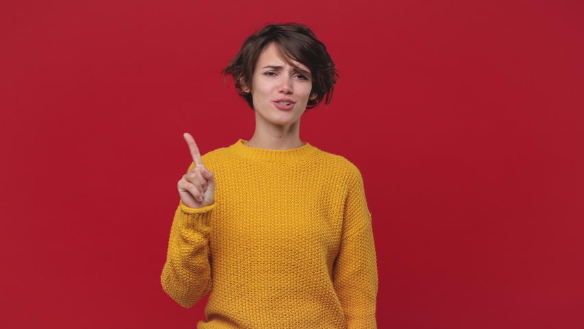 Fun young woman 20s years old in yellow sweater isolated on red wall background in studio. People lifestyle concept. Looking camera pointing fingers herself ask say who me no thanks i do not need it