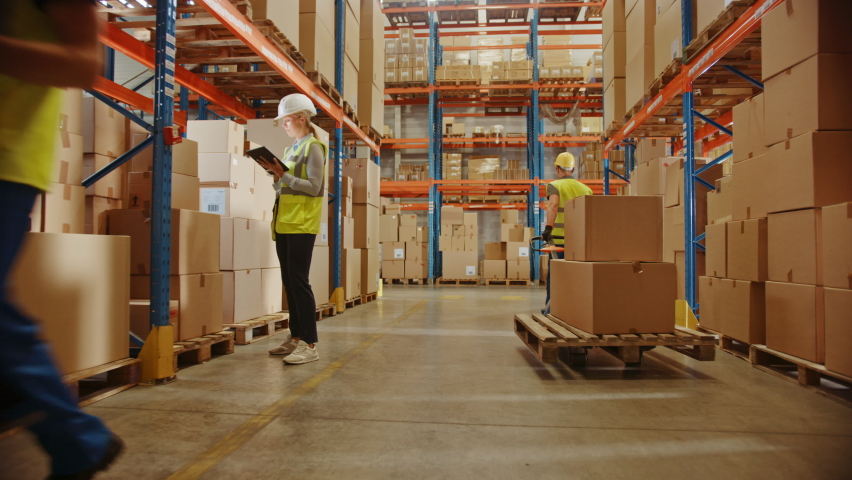 Retail Warehouse full of Shelves with Goods in Cardboard Boxes, Workers Scan and Sort Packages, Move Inventory with Pallet Trucks and Forklifts. Product Distribution Logistics Center. Ground Shot | Shutterstock HD Video #1060923340