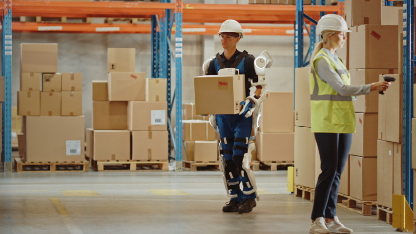 High-Tech Futuristic Warehouse: Worker Wearing Advanced Full Body Powered exoskeleton, Walks with Heavy Cardboard Box. Exosuit amplifies Human Performance, Strenght, Eliminates Work-Related Injuries Royalty-Free Stock Footage #1060923451