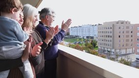 4k video of mother, son and grandparents clapping on the balcony in gratitude to the doctors