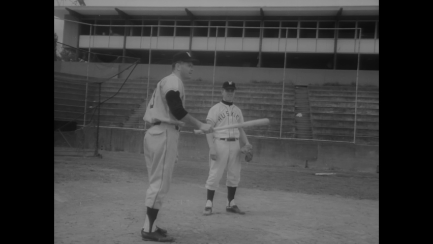 CIRCA 1963 - A baseball player at the University of Washington plays well on artificial legs.