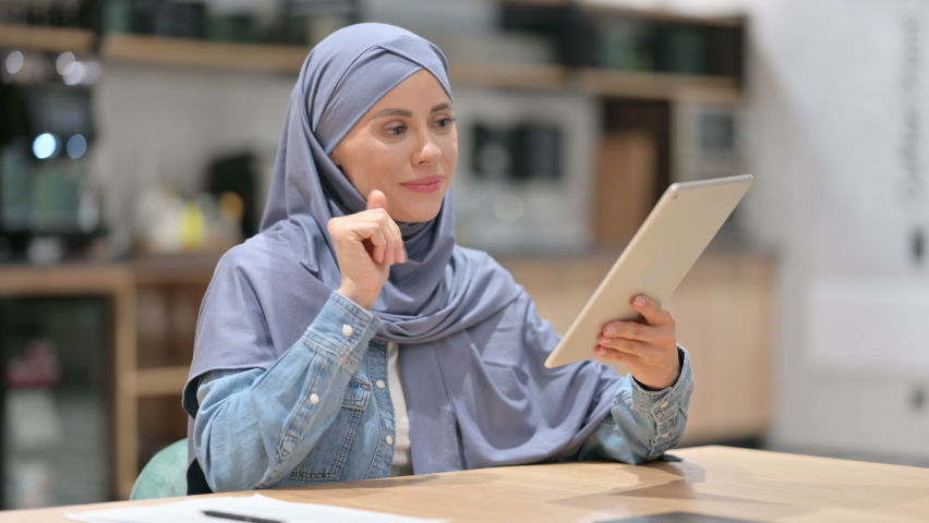 Online Video Chat on Tablet by Arab Woman at Work