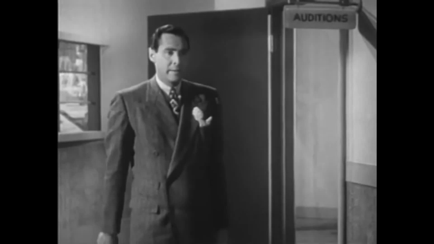 CIRCA 1946 - In this comedy movie, a broadcaster is reunited with his girlfriend and kisses her in the middle of the radio station.