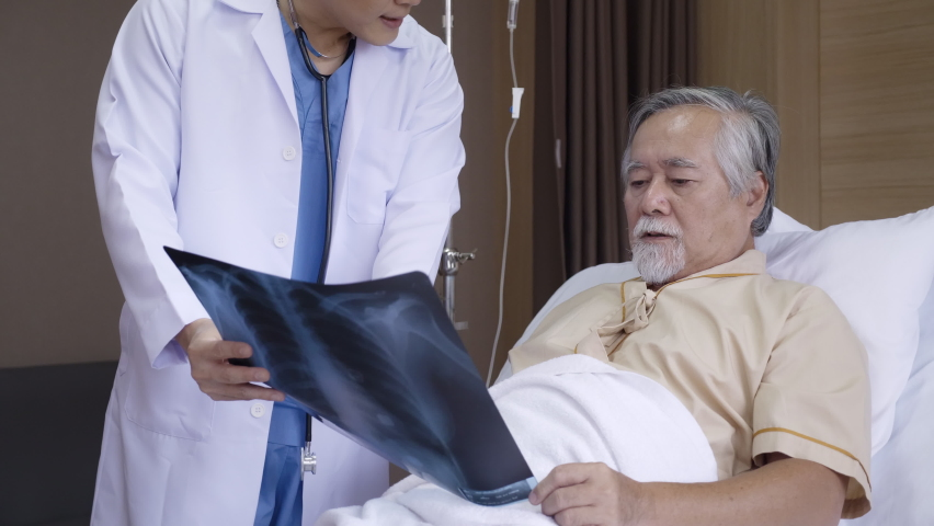 Doctor talking Consultant elderly male patient in hospital. Explain an X-ray about cancer treatment, lung disease and physical health. Retirement or Treatment health insurance. Concept Health care Royalty-Free Stock Footage #1060933516