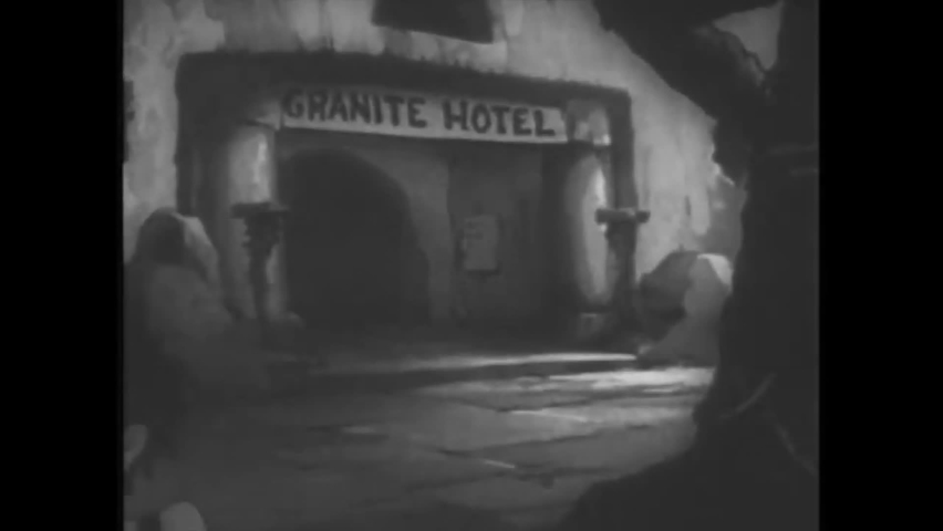 CIRCA 1940 - In this animated film, a ventriloquist performer and a gorilla check in at a stone age hotel.
