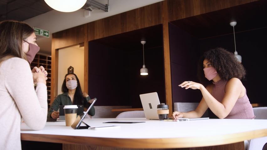 Businesswomen Wearing Masks Having Socially Distanced Meeting In Office During Health Pandemic | Shutterstock HD Video #1060940800