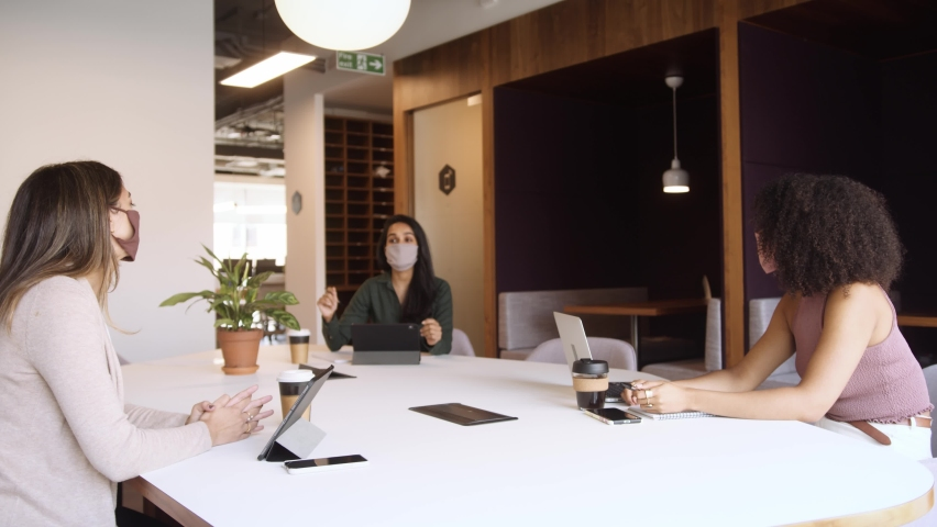 Businesswomen Wearing Masks Having Socially Distanced Meeting In Office During Health Pandemic