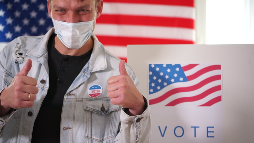Young patriot man in mask voted in a voting booth and shows a thumbs up sign. Sticker vote on the jacket. US elections 2020 concept