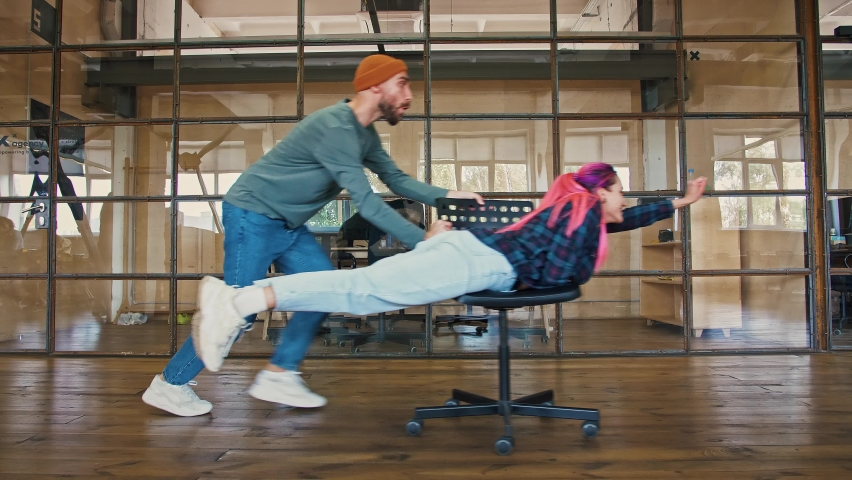 Office superhero. Young man riding his colleague woman with pink hair on chair pretending she is flying, side view