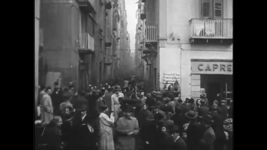 CIRCA 1940s - Italians and refugees undergo daily activities in overcrowded Naples after the allied occupation in the 1940s. Royalty-Free Stock Footage #1060951744
