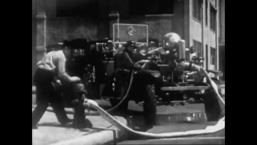 CIRCA 1940s - Firefighters use fire hoses to spray water to extinguish a fire and, later, they exit the building, in 1947.