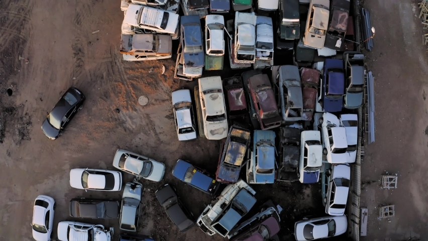 Aerial top view of the car dump with hundreds of cars stacked waiting to be recycled. A lot of unecological, harmful, old, wrecked cars are standing on the junkyard.