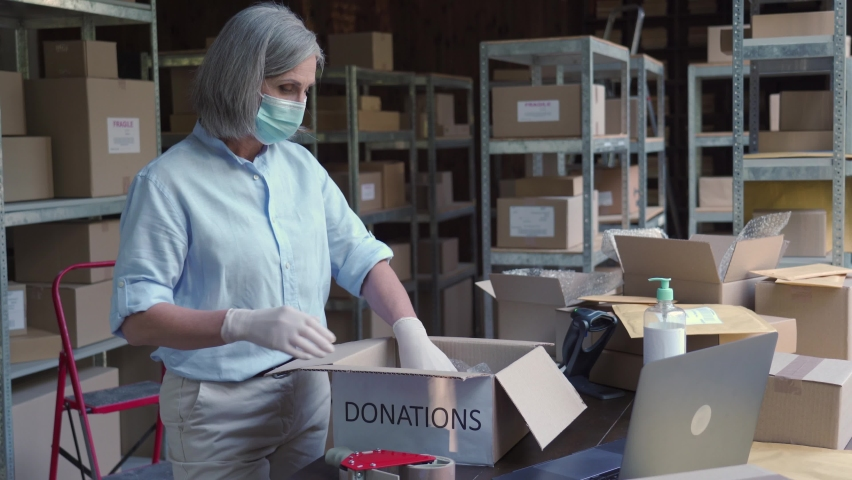 Mature female warehouse worker volunteer wearing face mask working in shipping delivery charitable stock organization packing donations box. Covid 19 coronavirus donating and volunteering concept. Royalty-Free Stock Footage #1060958170