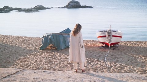 Young woman in a beige coat walks along the seashore. Girl with long hair in the boat parking lot. Sunny day on the coast. Sandy beach in a beautiful bay. Blue sea. Horizon line. Walk along the beach.