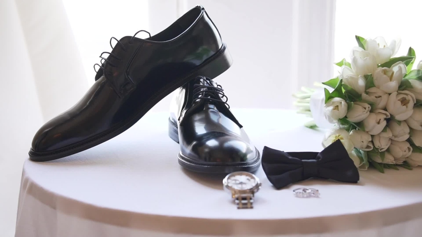 Detailed and themed photographed bridal shoe, flower, bow tie, watch and ring.
