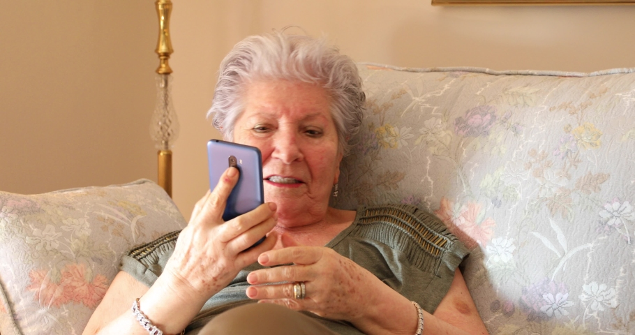 Portrait of a caucasian senior woman with white hair talking on her cell phone at home