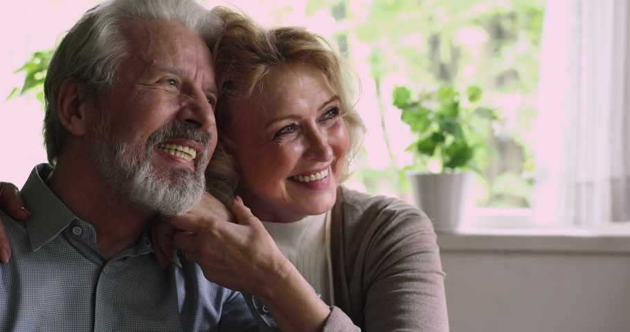 Close up happy elderly spouses sit together indoor hold hands day dreaming looking into distance. Loving husband kiss on cheek beloved 55s wife. Eternal love, welfare retired couple portrait concept