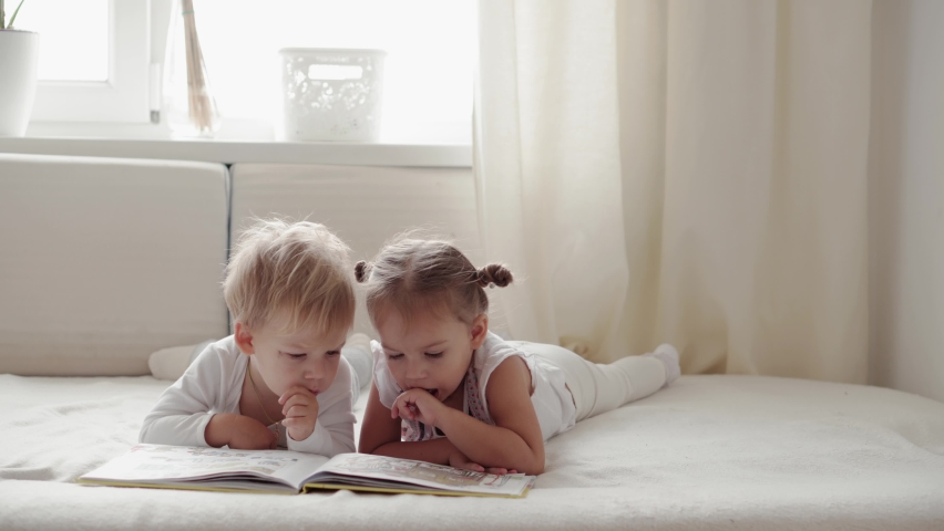 Friendship, family, education concepts  - Two smiling preshool, toddler children read large interesting book of fairy tales on bed. Siblings little twins have fun, happy kids on quarantine at home Royalty-Free Stock Footage #1060959370