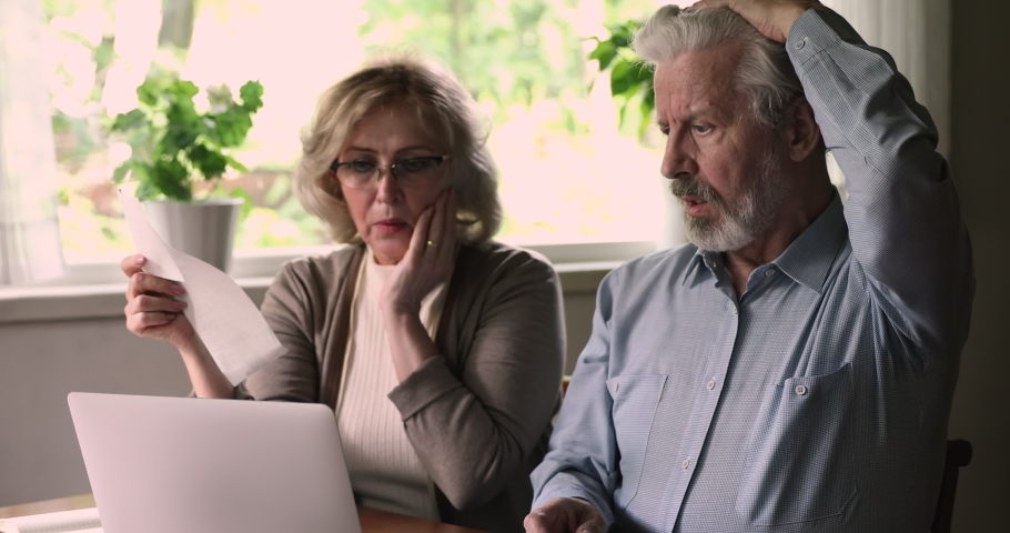 Stressed senior couple use e-bank app on laptop check utilities, feels shocked about unpaid taxes bank debt, having conflict discuss money overspend, high domestic bills, financial problems concept Royalty-Free Stock Footage #1060968127