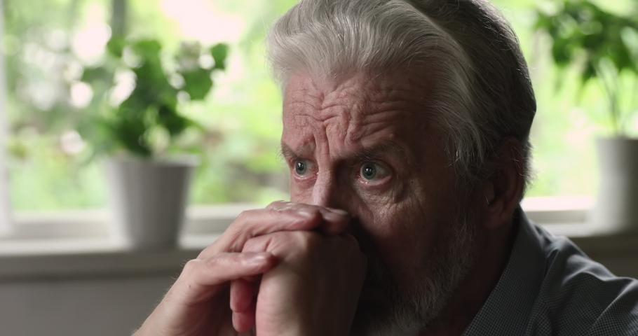 Close up face view of sorrowful grey haired old man widower mourning seated alone at home grieving feels desperate. Abandoned male at nursing house, dementia senile disease, mental disorder concept